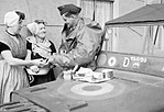 An RAF sergeant shares an alfresco lunch with two Dutch women at Nieuland, near Middelburg, soon after the town had been liberated by Allied forces, November 1944. CL1518.jpg