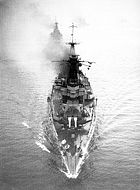 Photograph looking down on a large warship. The ship is travelling at speed, and is about to lead two or three other large vessels under the photographer.