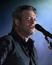 A man with greying harir and beard stubble, wearing a dark shirt, singing into a microphone