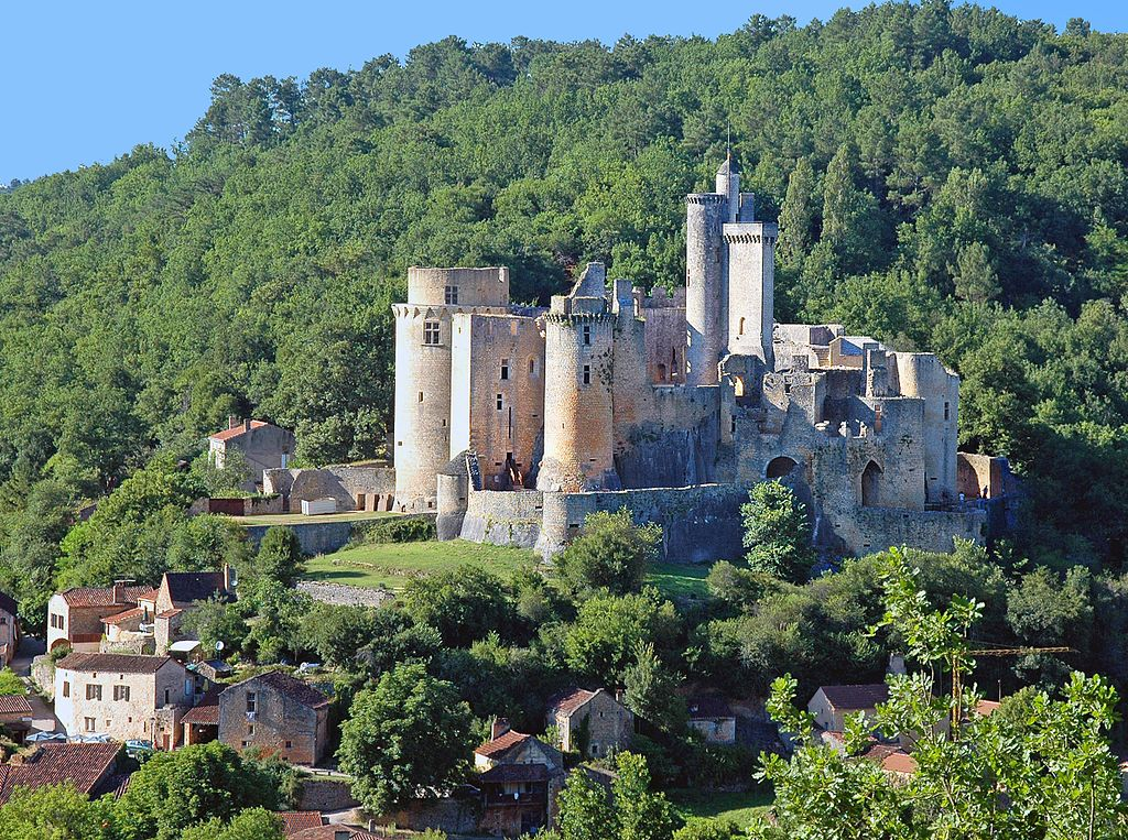Château de Bonaguil in France towering over nearby houses. The castle has large stone walls and towers and sits on a mountain surrounded by trees