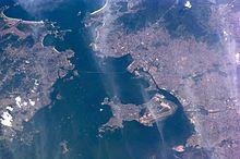 Imagem de satélite obtida no ano 2000, mostrando a Baía de Guanabara no sentido leste-oeste com a Região Metropolitana do Rio de Janeiro e a Ilha do Governador (ao centro). Os tons de cinza correspondem às zonas povoadas.