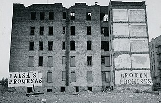 "White flight - Urban decay in the US: the South Bronx, New York City, was exemplar of the federal and local government's abandonment of the cities in the 1970s and 1980s; the Spanish sign reads ""FALSAS PROMESAS"", the English sign reads ""BROKEN PROMISES""."