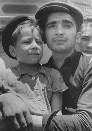 Aliyah Bet - Yisrael Meir Lau (aged 8) in the arms of Elazar Schiff, survivors of Buchenwald concentration camp on their arrival at Haifa, 15 July 1945