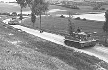 Four tanks move down a tree lined lane in open country.