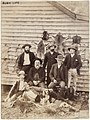 Bush men and dogs, with a wall of animal skins (including koala pelts), between 1870-1900.jpg