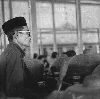 Kenong - Man playing kenong in a gamelan orchestra (1966)