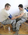 California Air National Guard Master Sgt. Darin Laity, left, gets his blood pressure taken by Tech. Sgt. Eliza Villa, both with 144th Fighter Wing, at Mirgorod Air Base, Ukraine, July 20, 2011 110720-F-VM449-032.jpg