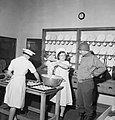 Captain Robert Russell of the US Army inspecting work in the kitchen of a NAAFI canteen in England during 1943. D17237.jpg