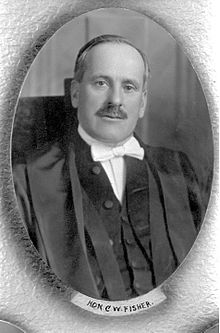 A formal portrait of a moustached man in formal robes and a white bowtie.