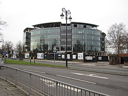 A photograph of a circular glass building with six storeys