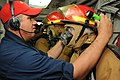 Chief Petty Officer Thomas Butler, left, adjusts a sailor's firefighting helmet during a fire drill aboard the guided-missile cruiser USS Hue City (CG 66) as the ship operates at sea on April 2, 2013 130402-N-OC961-129.jpg
