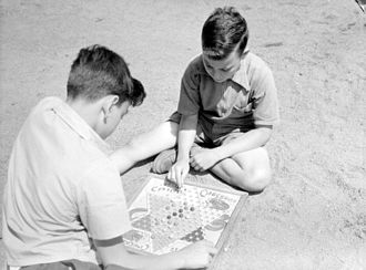 """Pressman Toy Corporation - Two boys playing to """"Hop Ching Checkers"""" (Chinese checkers) in a summer camp, Montreal, July 1942"""