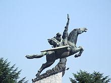 statuia unui cal înaripat văzut în profil, așezat în înălțime.  Animalul este întins înainte cu două persoane pe spate, prima persoană ridică un braț în aer