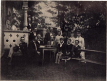 A black-and-white, slightly blurred photograph of a party outside a white house. To the left is a terrace, to the right a bench and in the middle a small table. There are many persons in the picture, who are formally dressed.