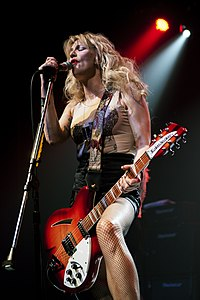 Blonde woman with a guitar singing into a microphone