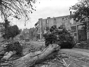 M3 Stuart - Light Tank M5A1 passes through the wrecked streets of Coutances.