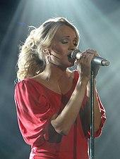 Молодая блондинка в розовом топе поет в микрофон