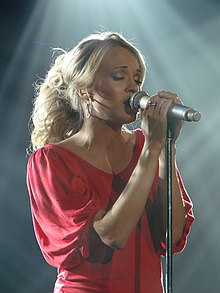 A young woman with blonde hair in a red top, holding a microphone and singing with her eyes closed.