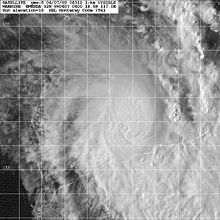 Satellite image of a weakening tropical cyclone. The cloud cover of the storm is becoming elongated to the north and east and constrained elsewhere. No eye is present within the storm. Part of Northwestern Australia can be seen at the bottom-right of the image.