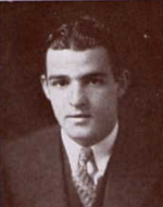 Man sitting in suit and tie, with hair parted.