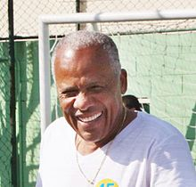 Middle-aged man smiling, with a football goal in the back