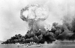 Long shot of mushroom cloud from an explosion, and black billowing smoke from nearby fire, with ship in foreground
