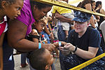 Defense.gov News Photo 110805-F-CF975-074 - U.S. Navy Petty Officer 2nd Class Tanya Carr puts a band on a patient s wrist before entering the Barranca Municipal Gym medical site during.jpg