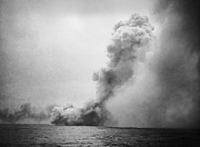 A black and white photograph showing a large cloud of smoke near the sea surface from which issues a towering mushroom cloud angled toward the right side of the photo