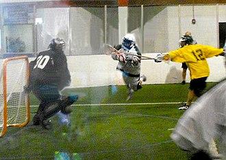 Box Lacrosse League - Columbus Brew player (white) sails past Detroit Coney Dogs' Owen Blank (yellow) as he attempts a dive shot on Coney Dogs goalie Devan Mighton (black) during 2012 season.