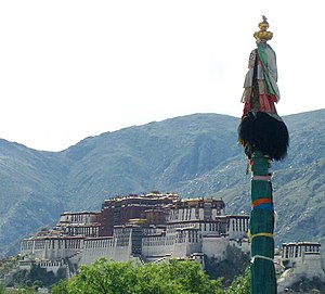 Dhvaja - Dhvaja (Victory banner) - pole design with silk scarfs, on the background the Potala Palace