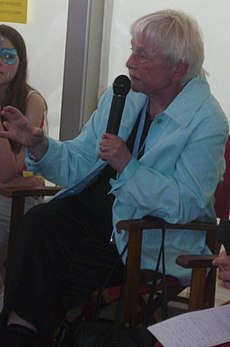 photo of Schüssler-Fiorenza, seated and speaking into a microphone