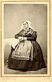 En kvinna poserar i en dräkt med huvudbonad till - Nordiska Museet - NMA.0039787.jpg