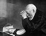 Grace, a black and white photo of a bearded man bowed in prayer