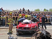 Emergency responders rescuing victims at a simulated car crash scene.