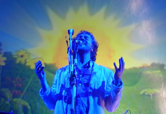 A man standing behind a microphone stand; a blue light is shining on him and a colorful, picturesque effect appears in the background.
