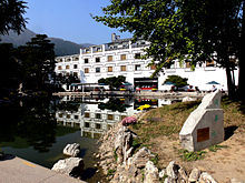 A white building with ornamented windows faces a lake ringed with rock structures. Trees appear around the structure.