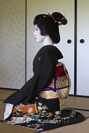 "Geisha - Profile of geisha Kimiha from Miyagawacho, wearing a formal black kimono (tomesode) and a Shimada-styled nihongami wig. Her obi is tied in the ""taiko"" (drum) style. All these are details which clearly distinguish her from a maiko (an apprentice)."