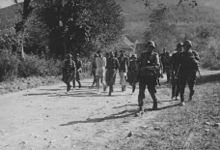 Soldiers escorting civilians with bound hands
