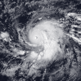 "Satellite image of a large, mature hurricane. The structure of the storm is similar to the number ""9"", with a single, large rainband curving into the center. At the center, there is a small, well-defined eye."