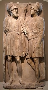 Stone slab with two men carved on it. They stand, wearing chitons.