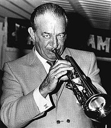 Black and white photo portrait of a man in a suit playing the trumpet