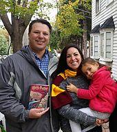 Un homme (à gauche) et une femme (à droite) avec une écharpe rouge et or et tenant une fillette dans ses bras (l'homme montre un livre Harry Potter au photographe et les trois personnes sourient)