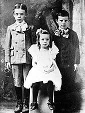Three small children; Long is on the far left, dressed in a child's suit