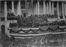Photograph of crowd in front of Capitol building decorated with patriotic bunting