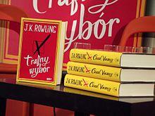 Une pile de trois livres au dos jaune est posée sur une table avec un exemplaire posé de face. La couverture de celui-ci est rouge encadrée de jaune. L'illustration est une simple case cochée d'une croix et le nom de l'auteure et le titre du livre sont écrits en blanc de part et d'autre de l'illustration.