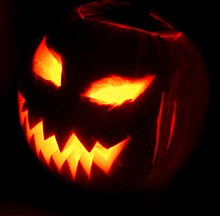A jack-o'-lantern.  The eyes and mouth of a carved pumpkina are lit from within while the rest of the carved vegetable is in darkness against a black background.