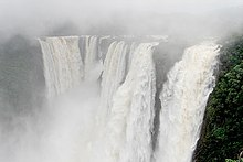 Wide photo of large waterfall in mist