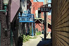 KFAI sign up and the rear of old buildings with brightly colored woodwork