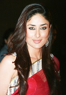 A young Indian woman. Her face is brightly lit. She has dark brown hair falling upto her chest and is clad in a red sari. Her eyes are bluish in color and she appears to be smiling while looking at the camera.