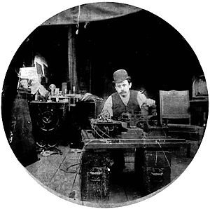 1890s - Charles Kayser of the Edison lab seated behind the Kinetograph. Portability was not among the camera's virtues.